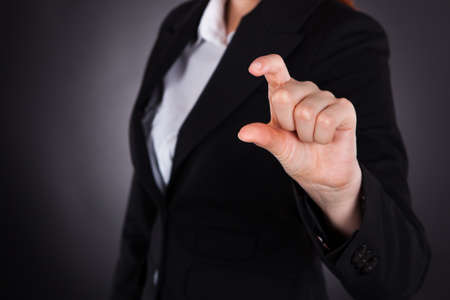 Midsection of young businesswoman showing small amount gesture isolated over black
