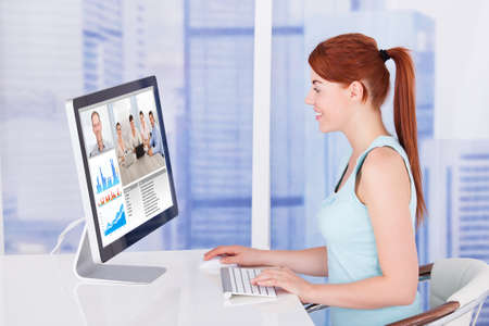 conferencing: Side view of young businesswoman video conferencing with team on computer at desk in office Stock Photo