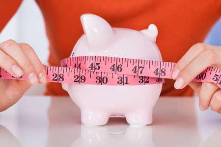 coinbank: Secci�n media de la mujer joven que mide hucha con cinta de medir en el escritorio