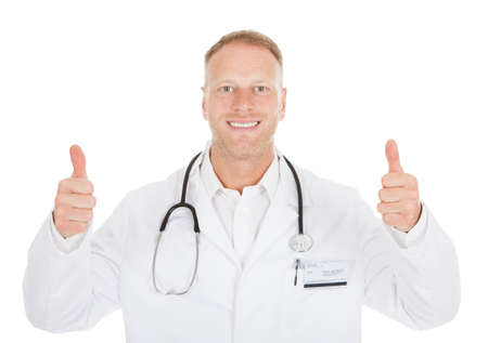 Portrait of smiling mid adult male doctor showing thumbs up over white  photo