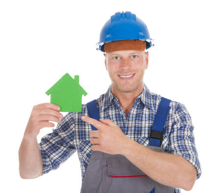 studio happy overall: Portrait of confident young male builder holding green house model over white background Stock Photo