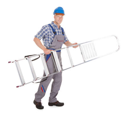 Full length portrait of confident manual worker carrying step ladder over white  photo
