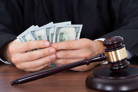 Midsection of male judge counting banknotes at desk in courtroom photo