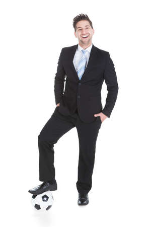 Full length portrait of confident young businessman holding soccer ball over white background photo