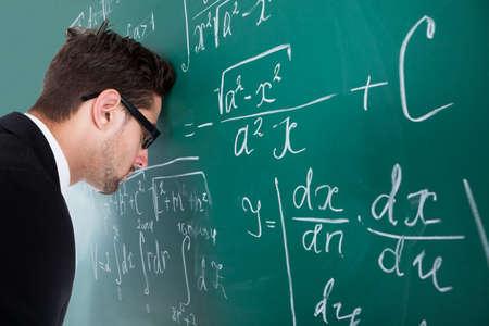 슬픈 젊은 남성 교수의 측면보기 교실 칠판에 머리를 기대어