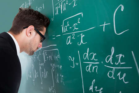 Side view of sad young male professor leaning head on blackboard in classroom
