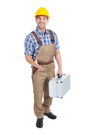 studio happy overall: Full length portrait of young manual worker with toolbox offering handshake over white  Stock Photo