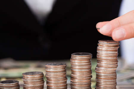 cropped image: Cropped image of businesswoman arranging coins as bar graph Stock Photo