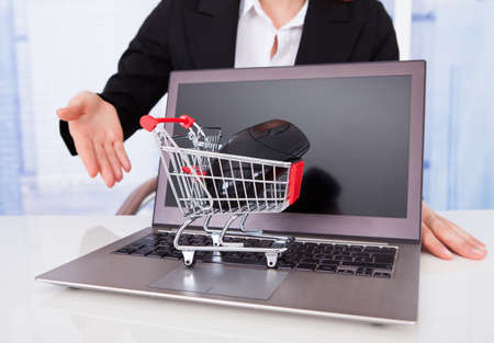 Midsection of businesswoman with shopping cart model and laptop at office desk photo