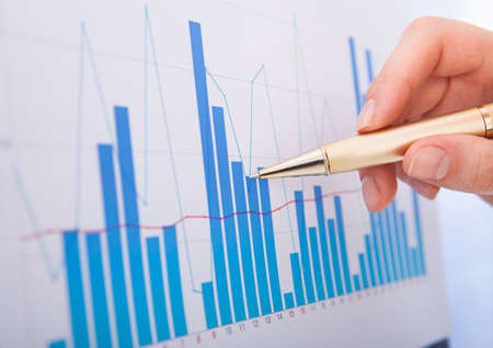 cropped image: Cropped image of businesswoman analyzing bar graphs Stock Photo