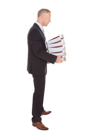 Side view of sad businessman carrying stack of binders over white  photo