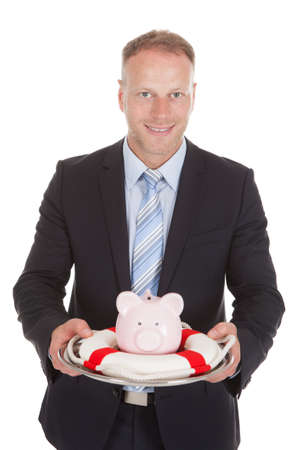 Portrait of smiling mid adult businessman protecting piggybank with lifebuoy over white  photo
