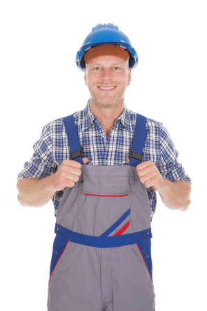 studio happy overall: Full length portrait of manual worker standing with hands on hip over white