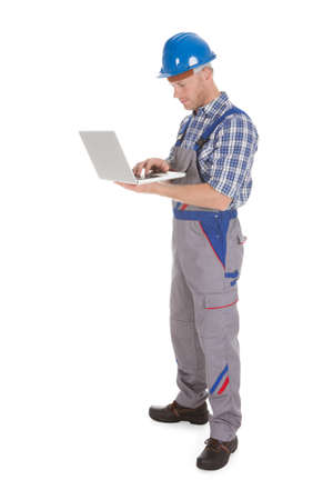 Smiling young manual worker using laptop over white  photo