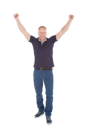 cheer full: Portrait of cheerful young man with hands raised standing isolated on white  Stock Photo
