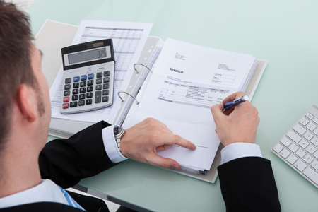 High angle portrait of young businessman calculating finance at office desk photo