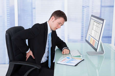 Young businessman suffering from backache at computer desk in office photo
