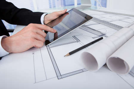 architect office: High angle view of male architect using digital tablet on blueprint in office