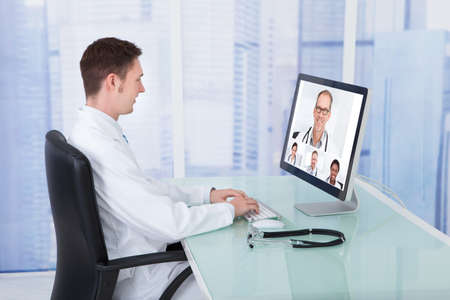 Young male doctor video conferencing with colleagues through computer in hospital photo