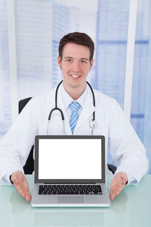 Portrait of confident young male doctor presenting laptop with blank screen at desk in hospital photo