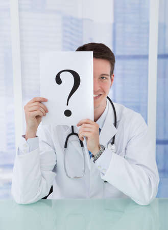 Portrait of smiling young doctor holding paper with question mark at desk in hospital photo