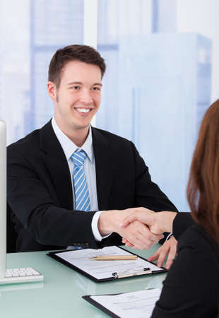 hire: Young businessman shaking hand of female candidate during job interview