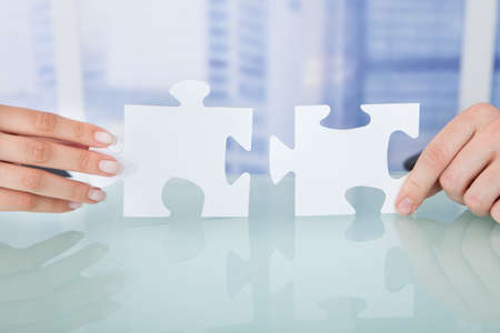 Cropped image of business people joining jigsaw pieces in office photo