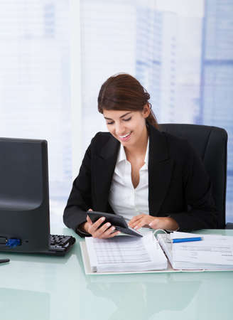 Portrait of confident young businesswoman using calculator at office desk photo