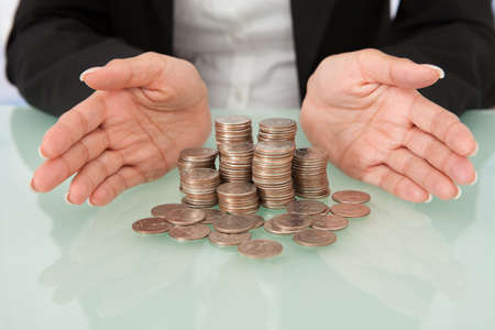 sheltering: Midsection of businesswoman sheltering coins in house shape on desk Stock Photo