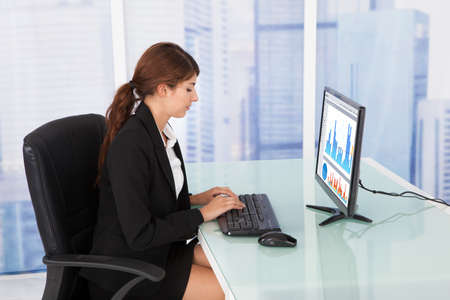 Portrait of happy businesswoman using computer at office desk photo
