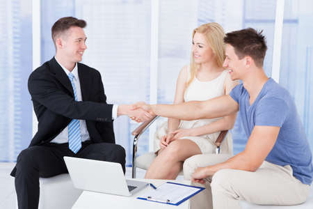 Young couple shaking hands with financial consultant in office photo