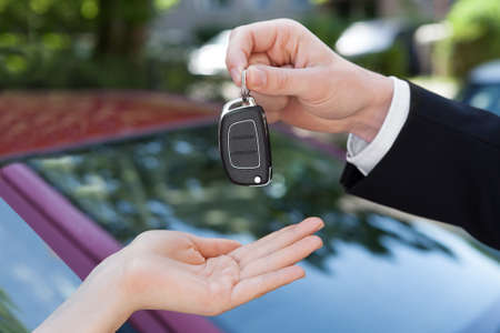 hand key: Cropped image of salesman handing key to woman by new car