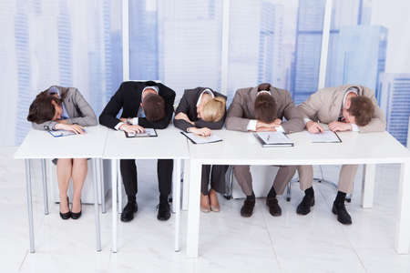 Group of tired corporate personnel officers sleeping at table in office Standard-Bild