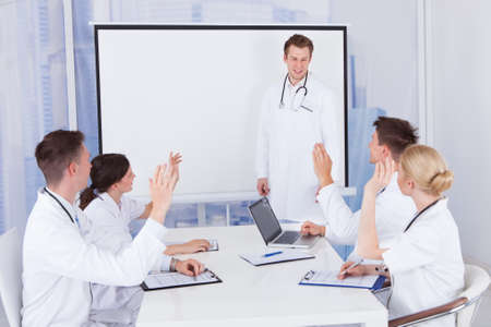 Team of young doctors clapping for colleague after presentation in hospital photo