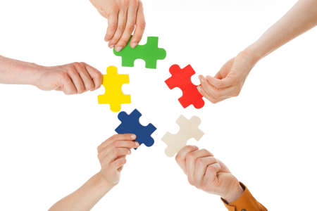 Closeup of young friends holding colorful jigsaw pieces over white