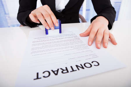 Midsection of young businesswoman using corporate seal on contract paper at office desk photo