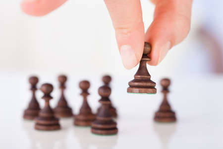 Cropped image of womans hand holding chess pawn on table photo