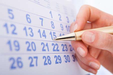 15 日のカレンダーをマークする女性の手のクローズ アップ