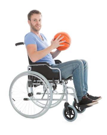 sportsperson: Full length portrait of disabled player holding basketball on wheelchair over white background