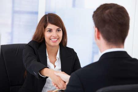 Empresaria joven estrechando la mano con pareja masculina en la oficina