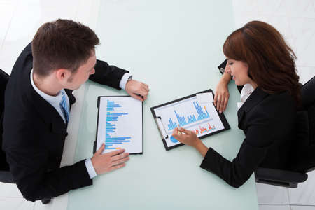 High angle view of young business people discussing over graphs in office photo