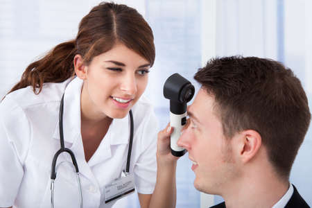 dermatologist: Young female doctor examining businessmans forehead with dermoscope in clinic Stock Photo
