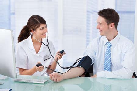 hipertension: M�dico de control de la presi�n arterial de sexo femenino joven de hombre de negocios en la cl�nica Foto de archivo