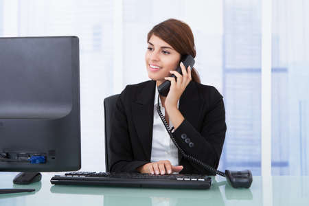 computer operator: Young businesswoman on call while using computer at desk in office