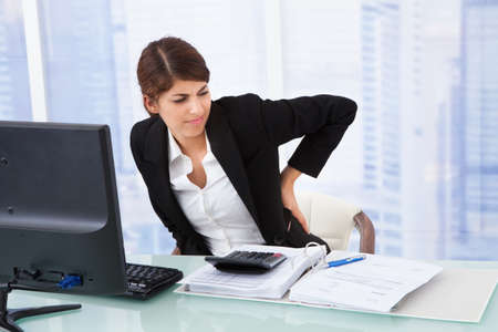 woman back: Tired young businesswoman suffering from backache sitting at computer desk in office Stock Photo