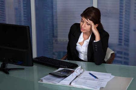 Stressed young businesswoman working at computer desk in office photo