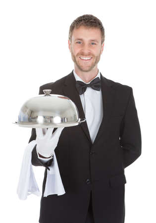 Portrait of confident waiter holding domed tray isolated over white