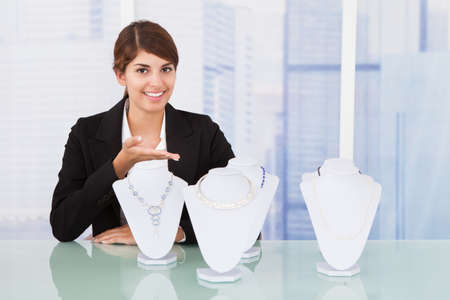 Portrait of confident saleswoman displaying jewelry at desk in office
