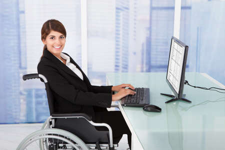 Side view portrait of handicapped businesswoman using computer while sitting on wheelchair in office Фото со стока