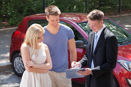 selling service smile: Young salesman showing contract paper to couple by new car